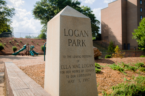"A stone monument inscribed with the words ""Logan Park in loving memory of Ella Mae Logan for her years of service to our community may 3rd 1987"""