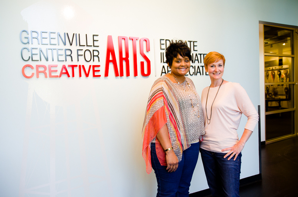 Two Women standing in the lobby of the Greenville Center for Creative Arts and smiling