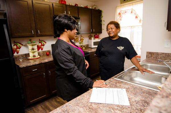 Crystal Corbin and Ms. Newkirk standing in a kitchen smiling at one another while paperwork rests on the counter