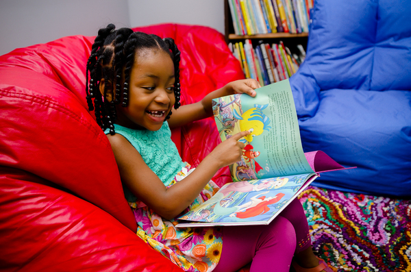 A young girl sits on a bean bag chair near a bookshelf as she points to a fish on the pages of a book she is holding up