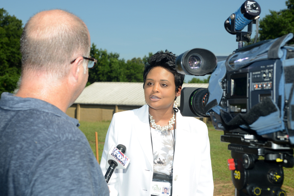 A woman standing in front of Manor at West Greenville and being interviewed by the local Fox affiliate