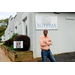 A man standing in front of a sign that reads Soteria - Community Development Corporation