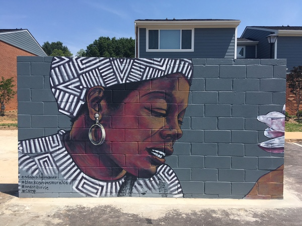 A mural painted on a wall of a woman wearing a bandana around her head
