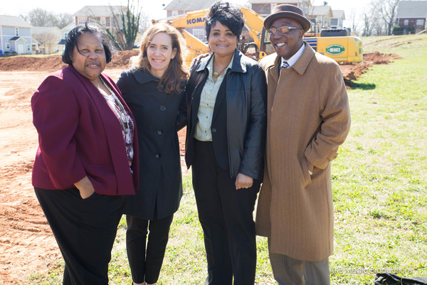 Three women and a man stand smiling in front of a backhoe