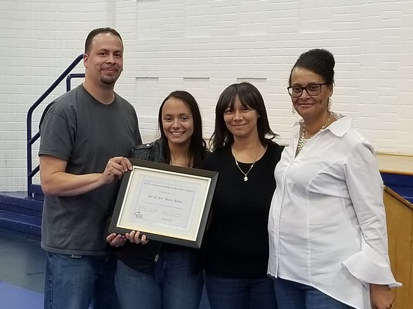 A man and three women hold up a framed certificate